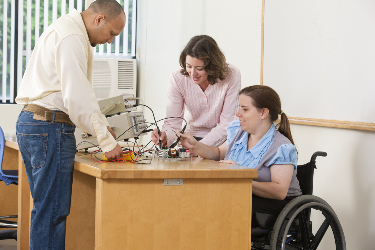 Photo of woman in wheelchair using oscilloscope probes and function generator.